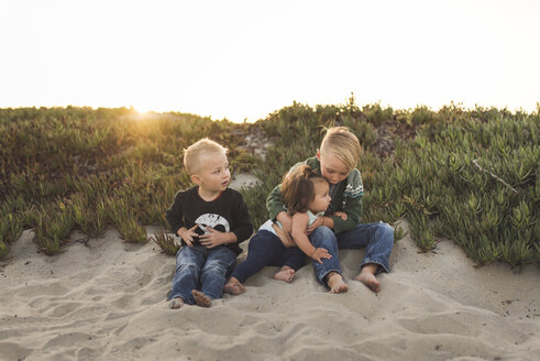 Full length of siblings sitting on sand at beach against clear sky during sunset - CAVF51093