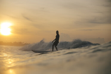 Silhouette man surfing on sea against sky during sunset - CAVF51108