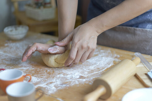 Midsection of woman kneading dough on table at home - CAVF51117
