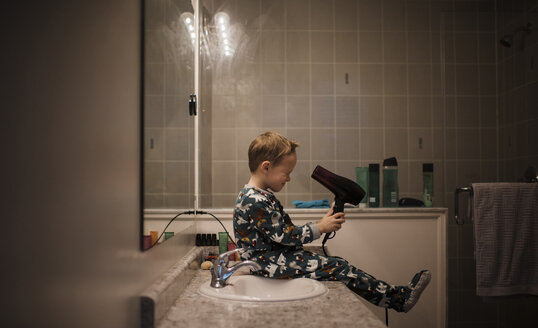 Side view of boy holding hair dryer while sitting by bathroom sink at home - CAVF51141