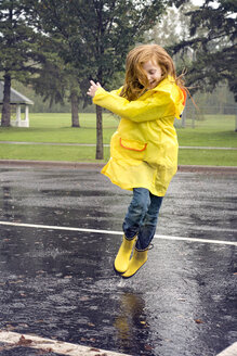 Cheerful girl wearing raincoat while jumping on road during rainfall - CAVF51144