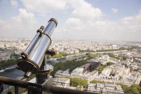 Coin-operated binocular on railing against cityscape - CAVF51160