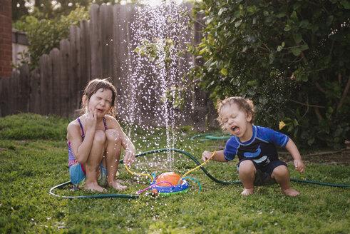 Siblings playing by fountain in yard - CAVF51181