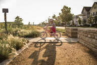 Side view of girl riding bicycle against clear sky during sunny day - CAVF51217