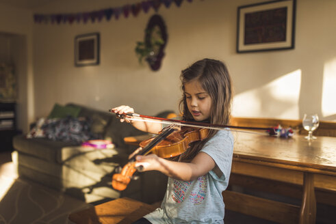 Girl playing violin while sitting by wooden table at home - CAVF51226