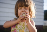 Close-up of girl eating apple while standing against wall - CAVF51241