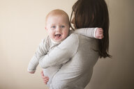 Portrait of cute brother carried by sister against wall at home - CAVF51244