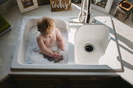 High angle view of shirtless baby boy sitting in kitchen sink at home - CAVF51247