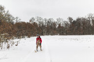 Teenage boy wearing snowshoes walking on snow covered field in forest against sky - CAVF51262