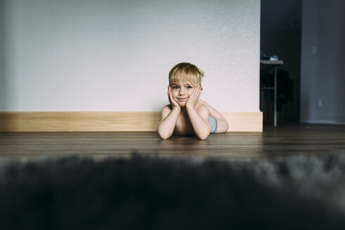 Portrait of shirtless boy with hands on chin lying on floor at home - CAVF51331