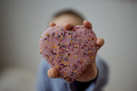 Boy holding heart shape sweet food at home - CAVF51355