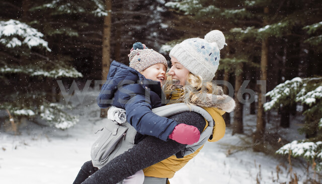 Happy mother carrying daughter in forest during winter - CAVF51358