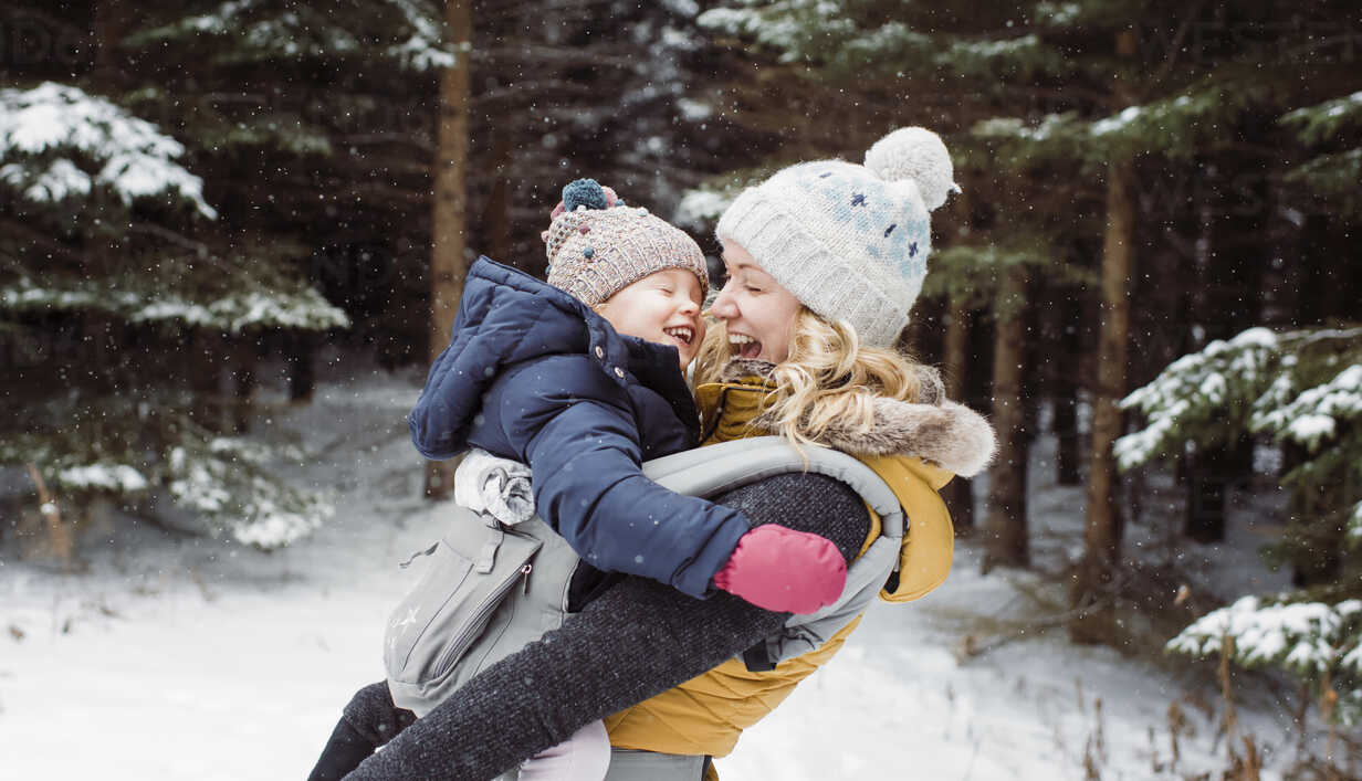 Happy mother carrying daughter in forest during winter - CAVF51358 - Cavan Images/Westend61