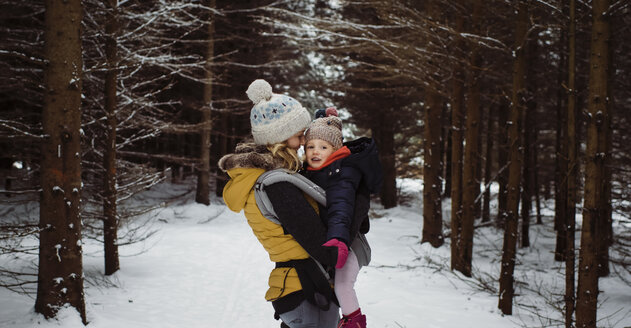 Mother carrying daughter while standing in forest during winter - CAVF51361