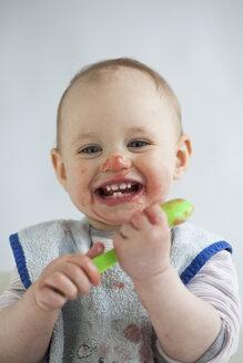 Portrait of laughing baby girl eating mush - JLOF00279