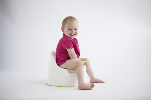 Portrait of laughing baby girl sitting on potty - JLOF00291