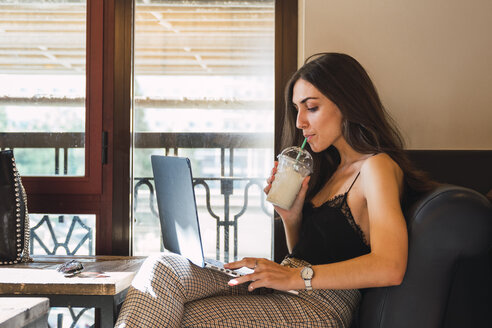 Young woman in a coffee shop drinking smoothie while using laptop - KKAF02811
