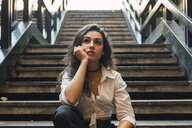 Portrait of young woman sitting on stairs - KKAF02820