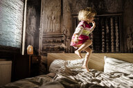 Little girl jumping on parent's bed at home having fun - PSIF00128