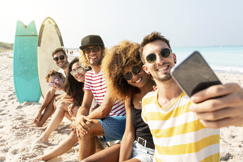 Friends sitting on the beach, having fun, taking selfies - WPEF00975