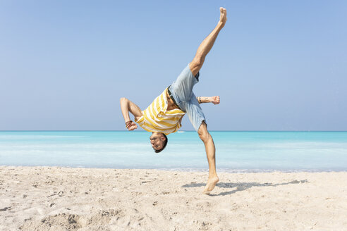 Young man doing a somersault on the beach - WPEF00978