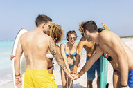 Group of friends on the beach stacking hands - WPEF00999