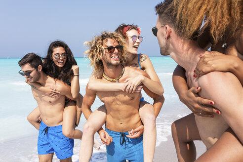 Friends walking on the beach, carrying girlfriends piggyback - WPEF01029
