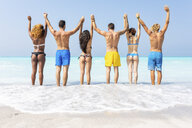 Group of friends at the beach, standing in the sea with arms raised - WPEF01047