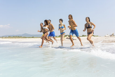 Group of friends having fun on the beach, running into the water - WPEF01053