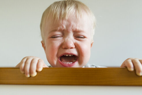 Close-up of baby boy screaming while crying in crib at home - CAVF51367