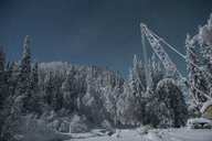 Low angle view of snow covered crane against star field - CAVF51394