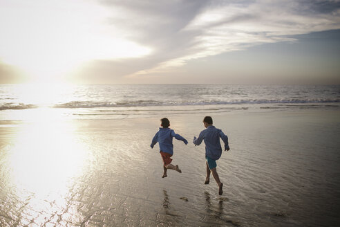 Rear view of playful brothers running at beach against sky during sunset - CAVF51412