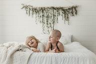 Siblings lying on bed at home - CAVF51448