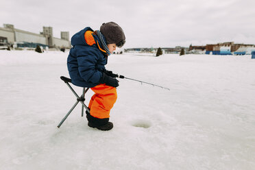 Side view of boy fishing in frozen lake while sitting on stool against sky - CAVF51454