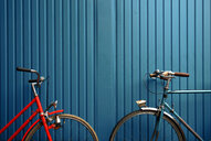 Symmetrical view of two bicycles against a blue background - INGF03531