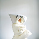 Studio shot of a man hiding in a white quilt on a white background - INGF03564