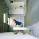 A man bending down in a building - INGF03606