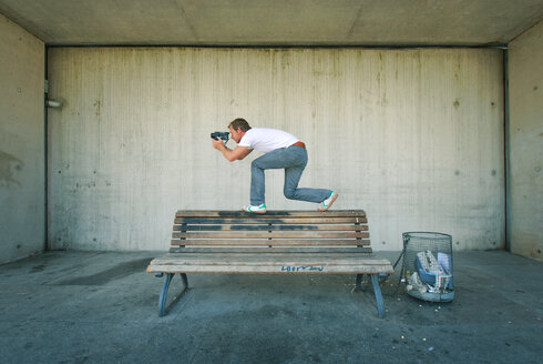 A man crouches on a bench whilst photographing - INGF03675