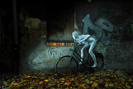 Creative shot of a man in a body suit riding a bicycle by a wall with graffiti on it - INGF03699