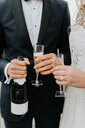 Bride and bridegroom holding champagne bottle and flutes - CUF46338