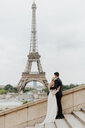 Bride and bridegroom, Eiffel Tower in background, Paris, France - CUF46341