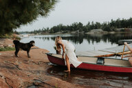 Couple and pet dog getting off boat, Algonquin Park, Canada - CUF46365