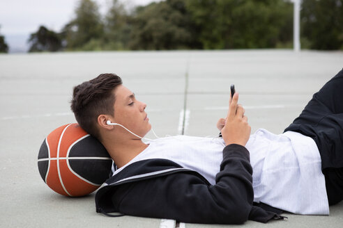 Male teenage basketball player lying on basketball court looking at smartphone - CUF46446