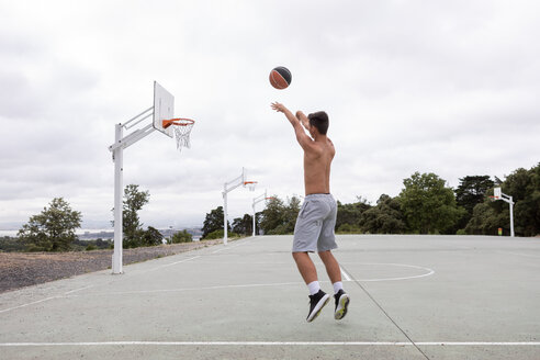Male teenage basketball player jumping and throwing ball toward basketball hoop - CUF46458