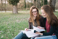 Girlfriends reading book in park - CUF46470