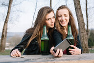 Girlfriends taking selfie with beer in park - CUF46476