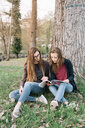 Girlfriends reading book in park - CUF46494