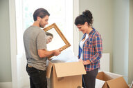Couple packing mirror into cardboard box - CUF46524