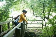 Hiker couple looking over wooden bridge - CUF46533