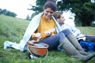Couple sitting in rural field cooking on barbecue grill - CUF46560